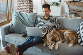 man and dog on couch with laptop