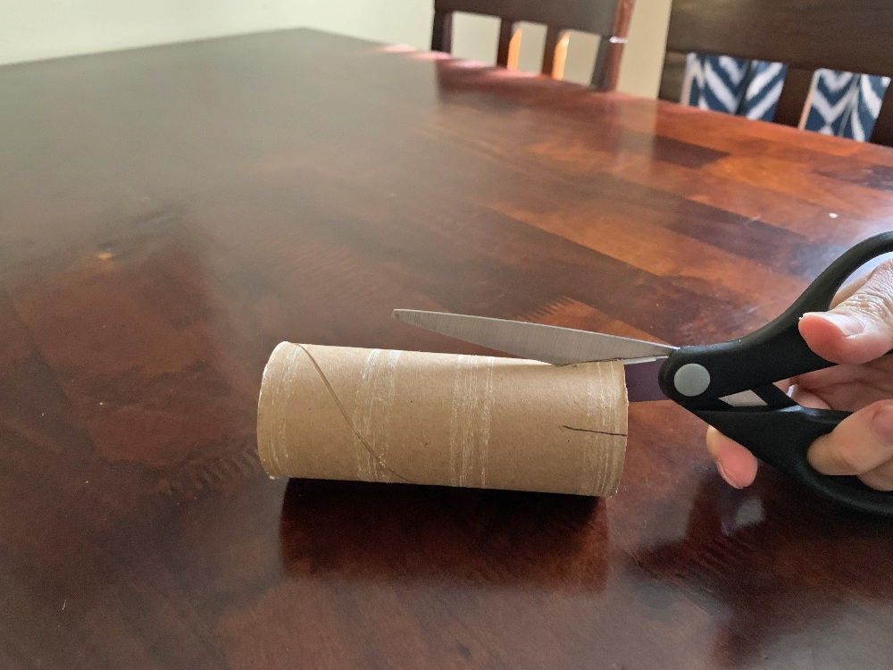 cutting slits in toilet paper tube with scissors