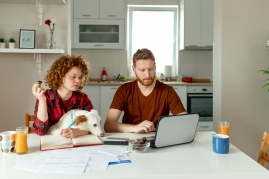 Couple does taxes at kitchen table with dog.
