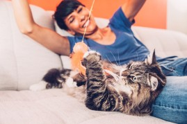 woman playing with cat
